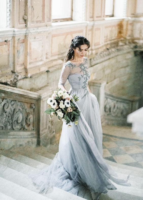 a beautiful light grey wedding dress with an embroidered illusion bodice, long sleeves and a layered skirt plus a train