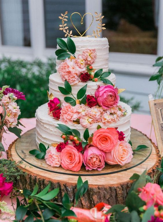 a beautiful wedding cake with pink, red and blush blooms, greenery, berries and a gold and elegant heart topper