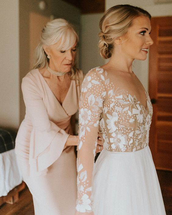 a blush fitting dress with a V neckline and bell sleeves plus pearls for a very chic and feminine mother of the bride look