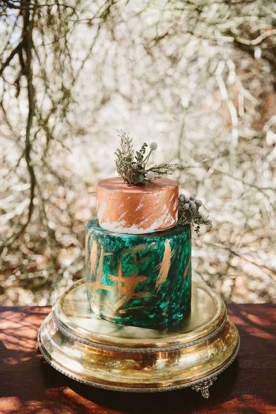 a boho safari wedding cake with brushstroke tiers, a copper and an emerald one, with greenery and berries