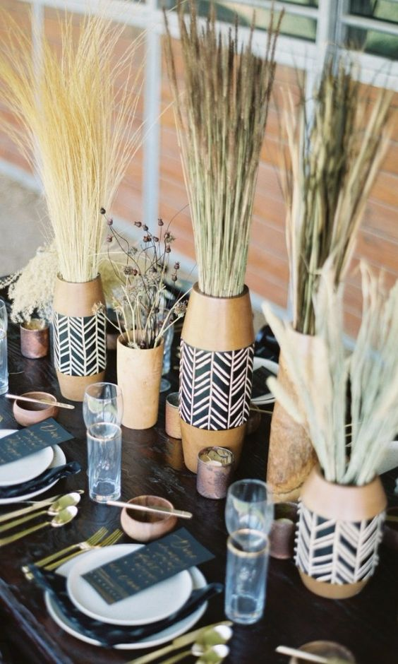 a boho safari wedding table setting with white porcelain, terracotta vases with boho wraps, grasses, candles and gold cutlery