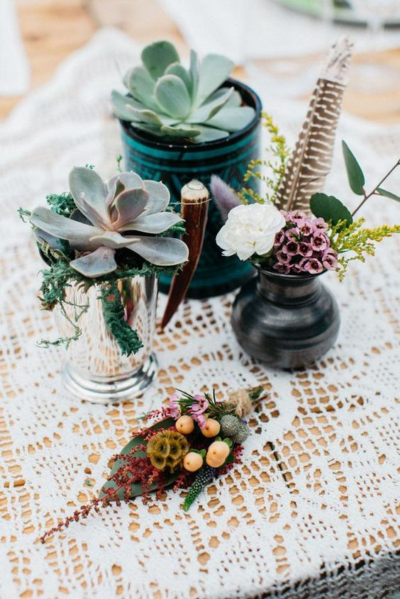a boho wedding centerpiece with succulents in vases, a vase with blooms and a feather