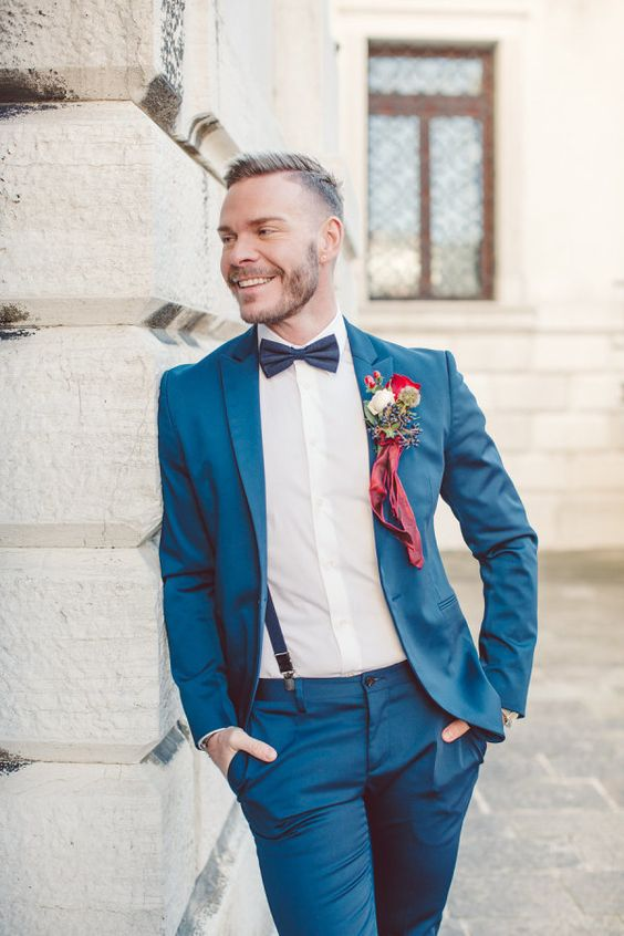 a bold blue suit, a black bow tie, black suspenders and a colorful boutonniere for a bright feel