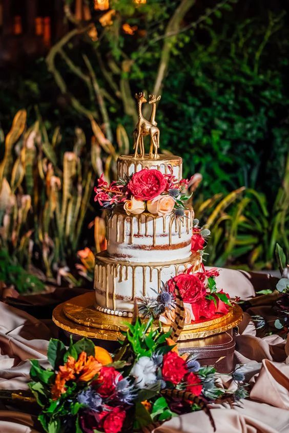a bold naked wedding cake with gold drip, bold blooms and gold giraffe toppers for a safari wedding