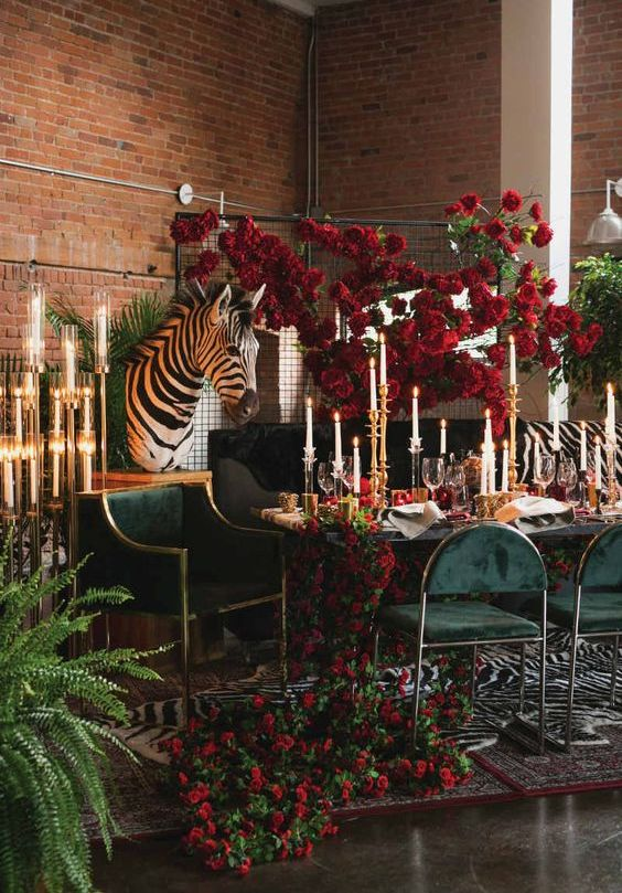 a bold safari-themed wedding reception with bold red blooms and greenery, candles and gold touches and a zebra