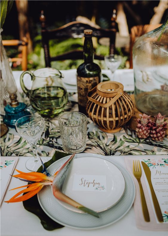 a bold safari themed wedding tablescape with a botanical runner, neutral plates, a wooden candle lantern and a green jug