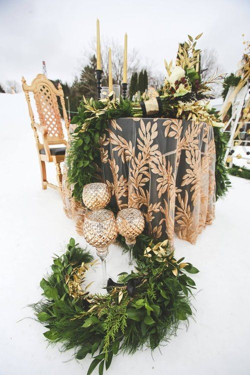 a botanical print tablecloth, a greenery table runner, candles, elegant candleholders for a snowy wedding