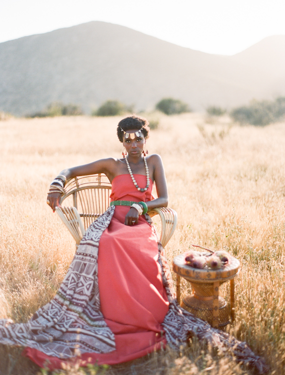 a bride wearing a coral strapless A-line wedding dress with an overskirt with African motifs and some statement accessories