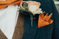 a bright fall outfit with a navy tweed suit, a brown waistcoat, an orange bow tie and handkerchief plus a neutral floral boutonniere
