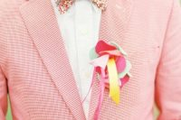 a bright pink gingham suit, a white shirt, a colorful floral bow tie and a bold fabric boutonniere for a touch of fun