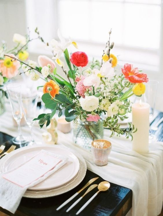 a bright spring wedding table with neutral linens, bright blooms, candles and gold cutlery and chic menus