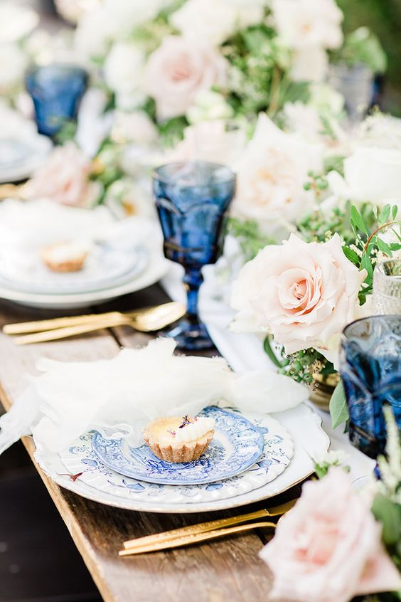 a bright spring wedding tablescape with blue printed plates and blue glasses, blush roses and greenery is very refined