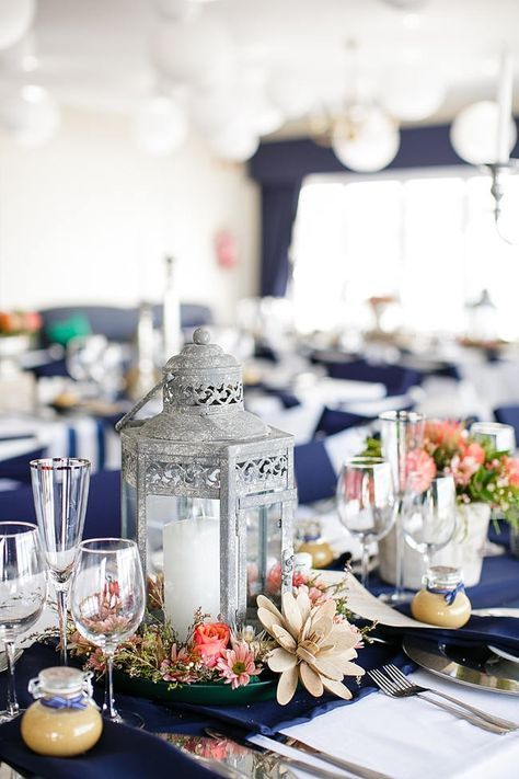 a bright tablescape with a navy tablecloth, a candle lantern, coral blooms and neutral succulents