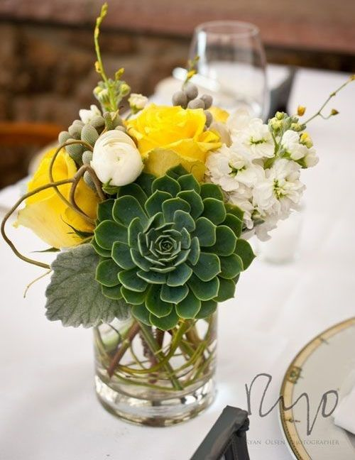 a bright wedding centerpiece with a large succulent, white and yellow blooms and berries