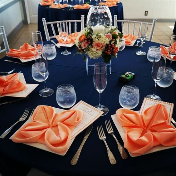 a bright wedding tablescape with a navy tablecloth, coral napkins and a coral and ivory floral wedding centerpiece