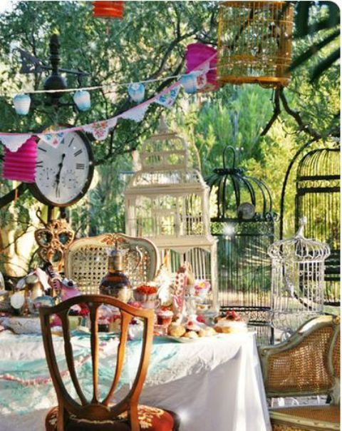 a brigth Mad Hatter setting with colorful buntings, clocks, lots of cages and bright porcelain