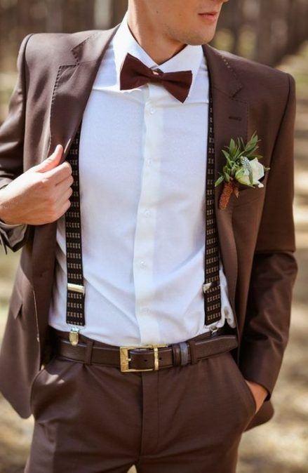 a brown suit, a white shirt, brown printed suspenders and a floral boutonniere for a fall groom's look
