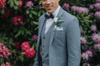 a checked blue three-piece suit, a white shirt, a navy polka dot bow tie plus a white floral boutonniere