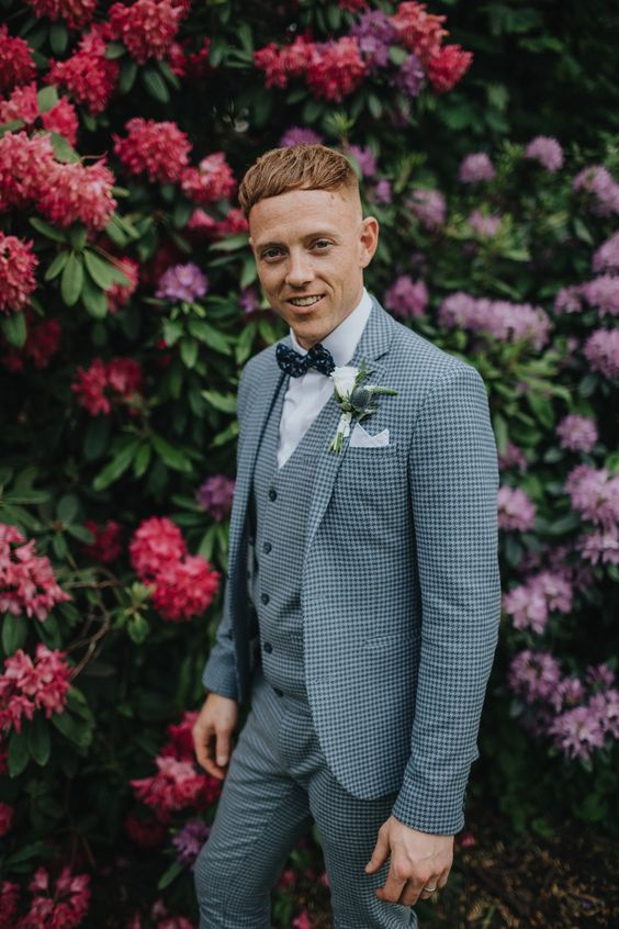 a checked blue three piece suit, a white shirt, a navy polka dot bow tie plus a white floral boutonniere