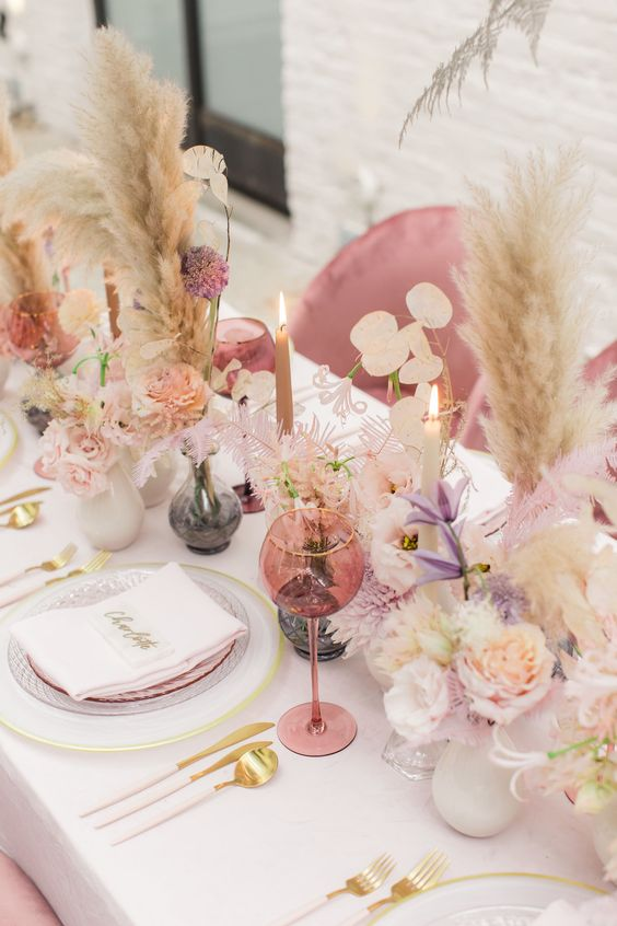 a cheerful spring wedding tablescape with pink glasses, pampas grass, gold cutlery and lilac blooms