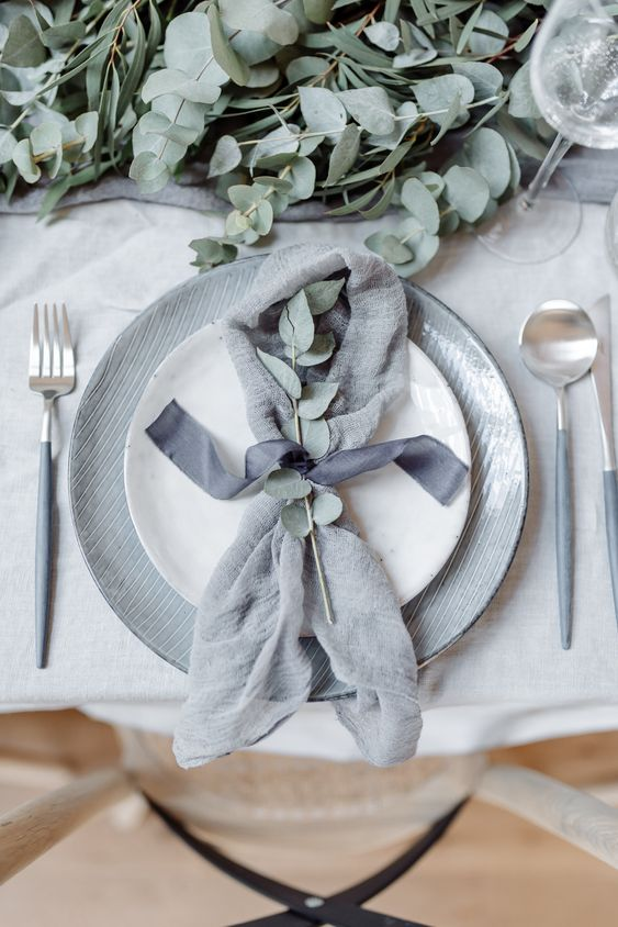 a chic minimalist wedding tablescape with a grey table runner, grey plates, eucalyptus and grey cutlery