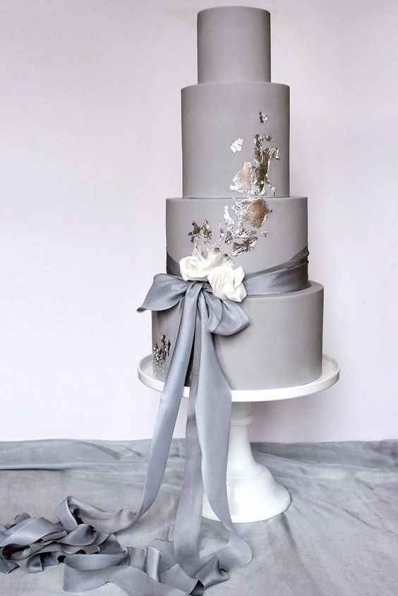 a chic plain grey wedding cake with silver leaf, a grey and white silk ribbon bow is a modern and stylish piece