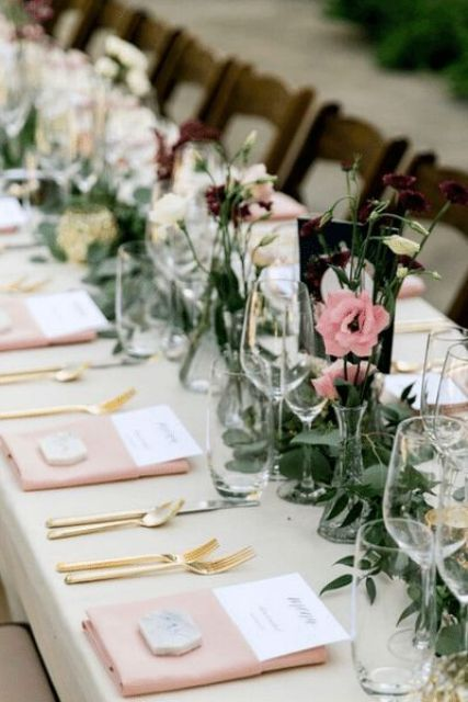 a chic spring wedding tablescape with pink and neutral blooms and greenery, pink napkins, gold cutlery and glasses