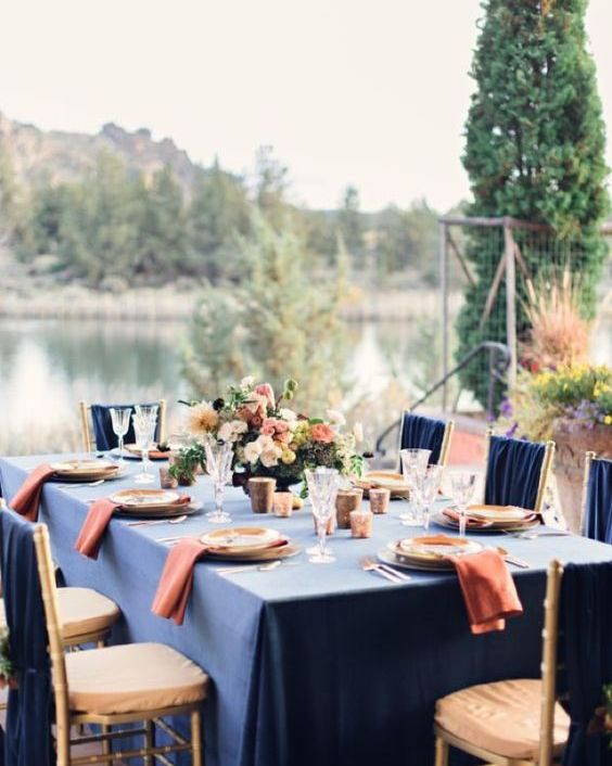 a chic tablescape done with a navy tablecloth, coral napkins, gold touches and coral and ivory blooms