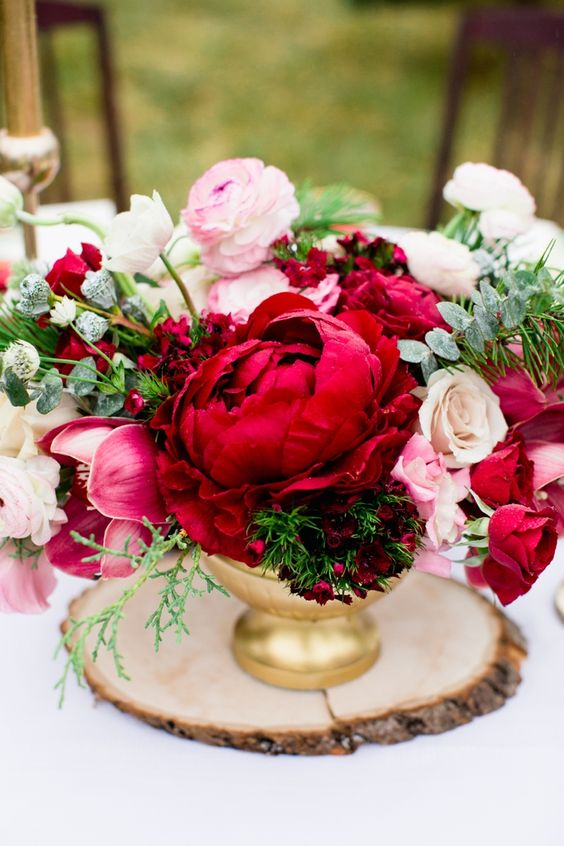 a chic wedding centerpiece of a gold vase, deep red, pink and white blooms and greenery for texture