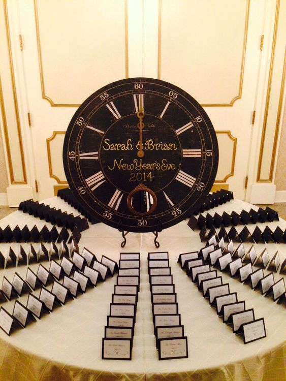 a chic wedding escort card table with a large black clock and metallic touches looks wow