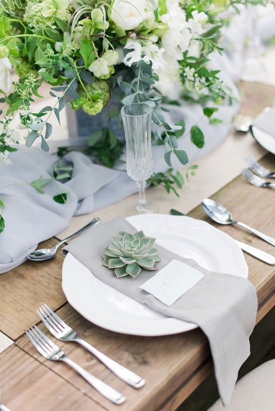 a chic wedding tablescape with a light grey table runner and napkin, greenery, succulents and elegant silver cutlery