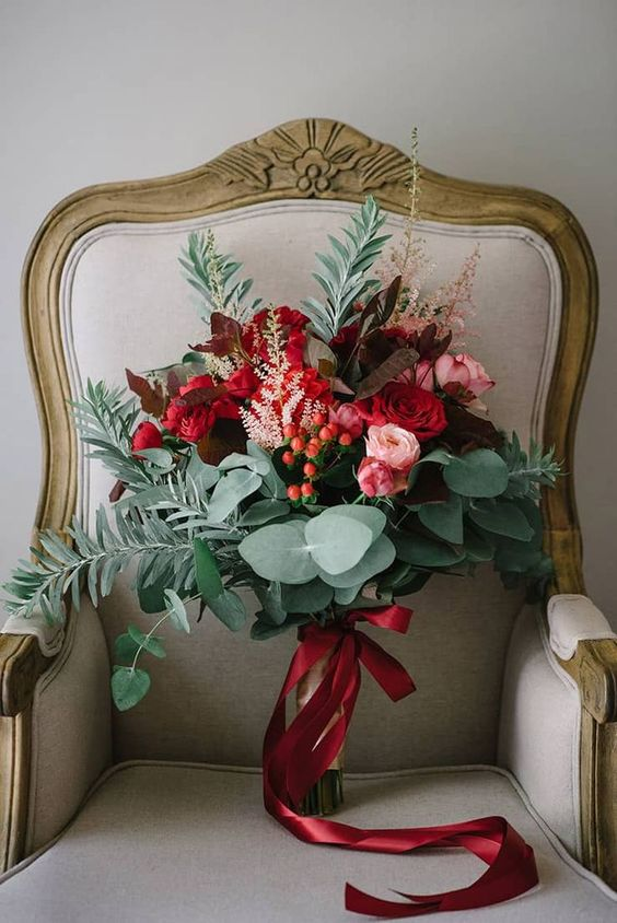 a colorful wedding bouquet of pink and red blooms, foliage and berries plus red ribbons