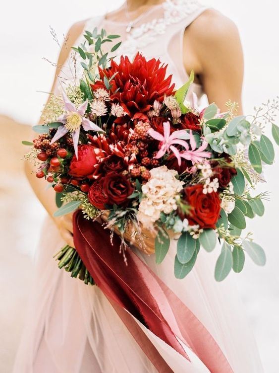 a colorful wedding bouquet of red and pink blooms, berries, foliage and long red and pink ribbons