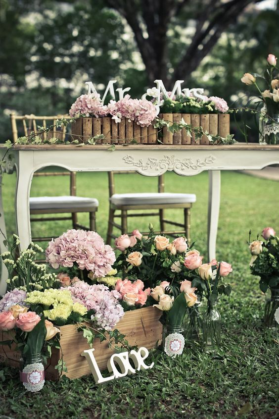 a crate with blooms, letters, a crate with blooms and letters on the table to accent a garden sweetheart table