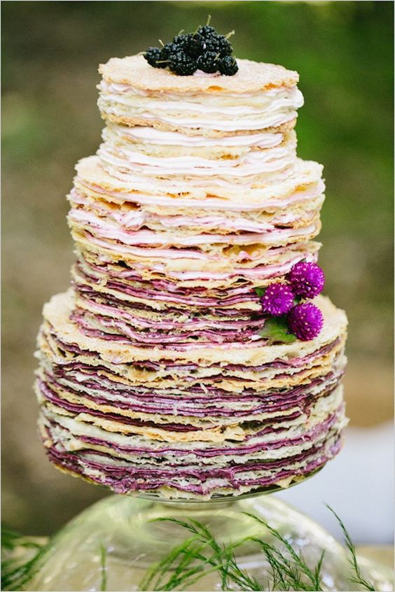 a crepe wedding cake with berry cream and fresh berries and blooms on top feels very summer-like