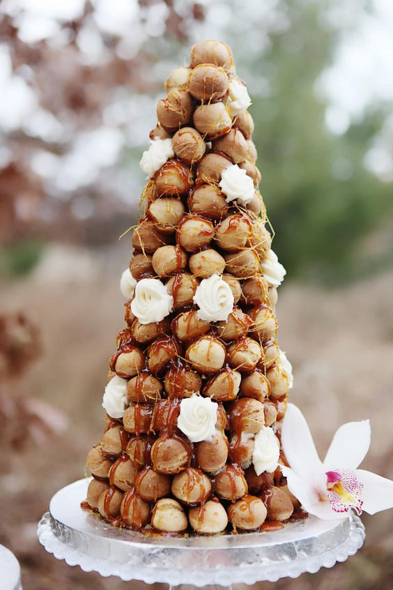 a croquembouche topped with caramel and with fresh white blooms is a refined idea