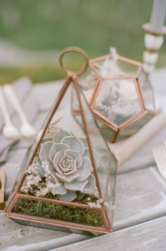a cute copper terrarium with moss, wildflowers and a pale succulent is a chic and stylish wedding centerpiece idea