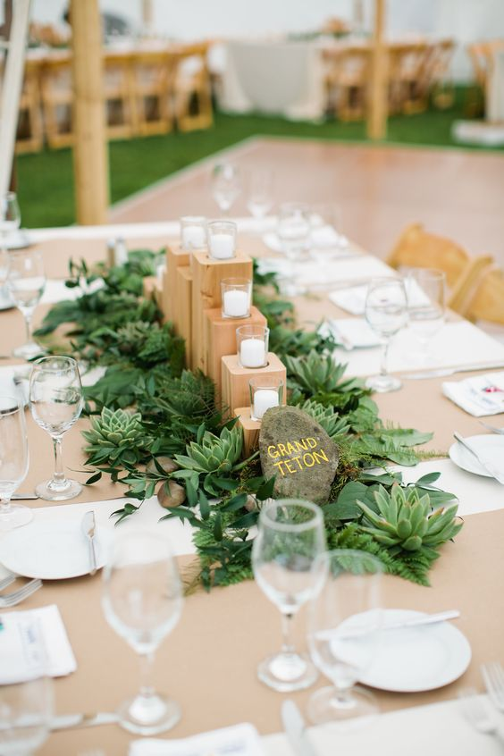 a cute natural wedding centerpiece with succulents, greenery, a large pebble, wooden stands and candles