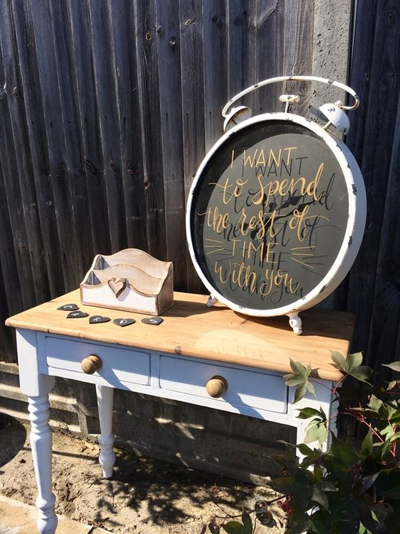 a cute wedding card table done with an oversized clock with a romance quote is pure love
