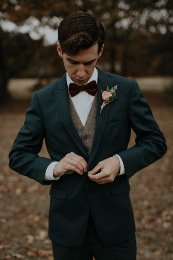 a dark grey suit, a beige waistcoat, a white shirt and a plum colored bow tie for a vintage feel