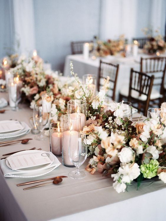 a delicate spring wedding tablescape with neutral linens and neutral blooms with dark foliage, blush candles and chic cutlery