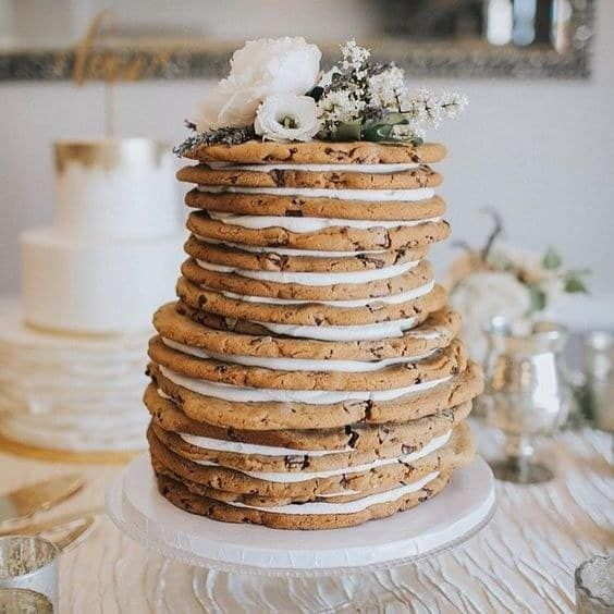 a delicious wedding cake made of large cookies and cream plus some blooms on top is totally non-traditional