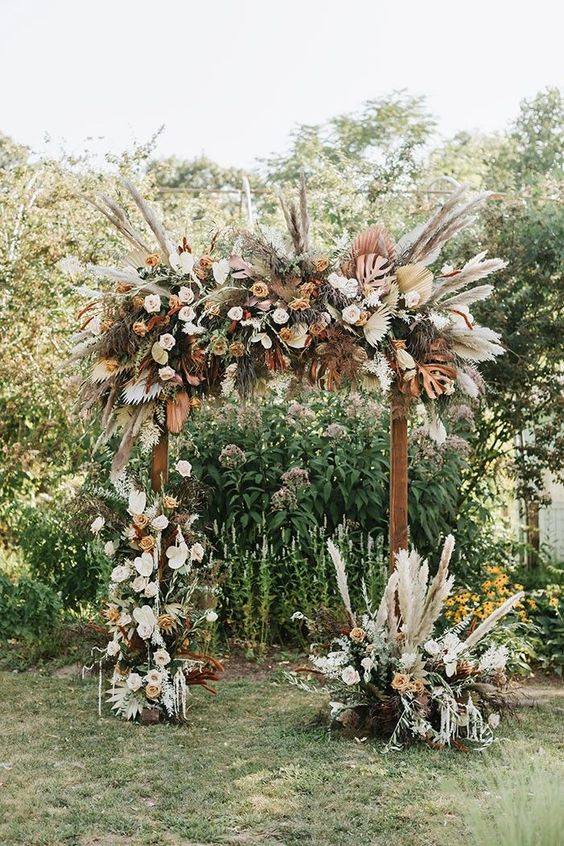 a dimensional and textural safari wedding arch with lots of pampas grass, fronds, peachy, blush and white blooms