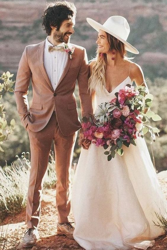 a dusty pink suit, a white shirt, a plaid bow tie and two tone shoes for a summer groom