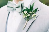 a fresh spring groom's outfit with a dove grey suit, a sage green bow tie and a greenery and neutral floral boutonniere