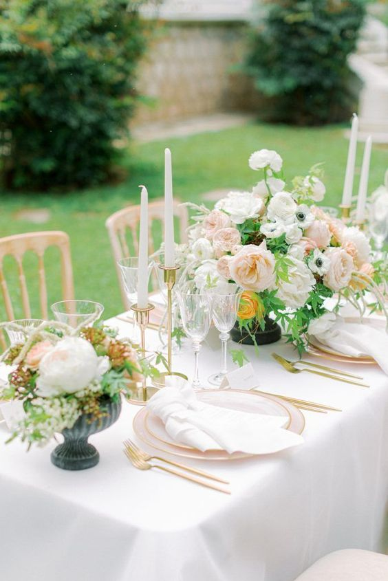 a fresh spring wedding tablescape with pink plates, blush and white blooms, white candles and gold touches