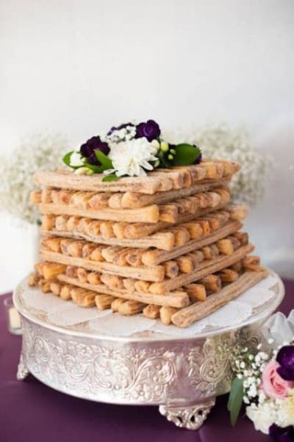 a fun and cozy churros wedding cake topped with fresh blooms is a tasty idea, add some dips around