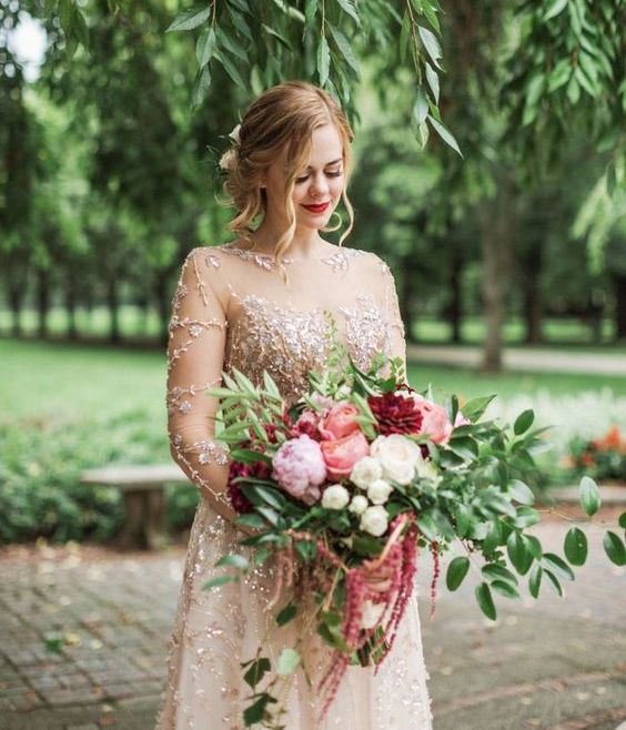 a gold embellished wedding dress paired with a lush wedding bouquet with pink, burgundy, blush blooms and greenery