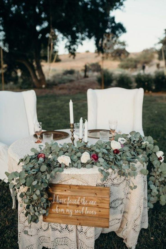 a greenery and blush and burgundy bloom table runner, a sign and some candles to mark the table