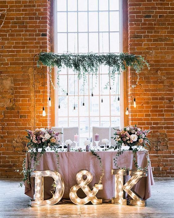 a greenery and bulb installation, lush pastel florals and marquee monograms to highlight the sweetheart table